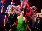 Dance party with group people dancing. Women and men have fun in night club. Happy girl with tousled poster