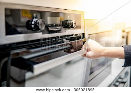 poster of Male Hand Opening Oven Door In The Kitchen Showroom. Buying Cooking Appliance For Domestic Kitchen.
