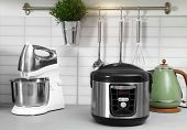 Modern Multi Cooker And Kitchen Appliances On Table poster