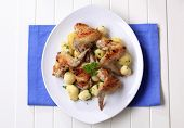 Five baked chicken wings with potatoes on a white oblong plate