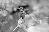 Black and White photo of  Tilt shot of happy mid adult couple boating in lake during summer poster