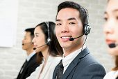 Smiling Male Asian Customer Service Telemarketing Agent Working In Call Center With His Team poster