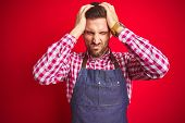 Young handsome man wearing shop owner apron uniform over red isolated background suffering from head poster