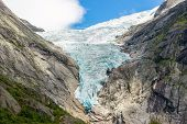 Briksdal Or Briksdalsbreen Glacier With Melting Blue Ice, Norway Nature Landmark And Its Lake Of Mil poster