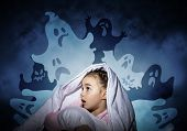Excited Girl Hiding Under Blanket From Imaginary Ghosts. Scared Kid Sitting In His Bed At Home. Litt poster