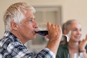 Happy senior man drinking a glass of red wine during lunch. Old man enjoying wine with friends in ba poster