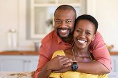 Happy mature black couple bonding to each other and smiling while sitting on couch. Portrait of smil poster