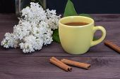 Yellow Cup Of Tea With Cinnamon On A Dark Wooden Table Decorated With A Branch Of White Lilac. A Ple poster