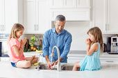 Caucasian Father Dad Gives Children Daughters Fresh Fruits To Eat. Happy Family In Kitchen Eating. O poster
