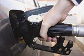 close-up of a mens hand refueling a car at a gas station (Fuel Pump)