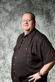 stock photo of portrait middle-aged man  - overweight middle age man against portrait backdrop - JPG