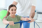 Professional Physiotherapist Working With Female Patient In Rehabilitation Center poster
