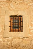 picture of scrappy  - An old window with wrought iron bars cased into stone - JPG
