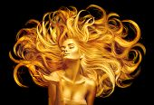 Gold Woman. Beauty fashion model girl with Golden make up, and Long hair pointing hand on black back poster