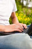Man - only torso - is working on his laptop outdoors; presumably it is his garden