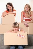 three young women posing in a room full of unpacked packages