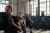 Group of three people doing squats while holding heavy medecine balls. Young men and fitness woman d poster