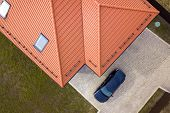 Aerial Top View Of House Metal Shingle Roof With Attic Windows And Black Car On Paved Yard. poster