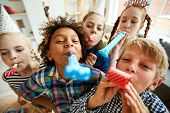 High Angle View At Multi Ethnic Group Of Children Blowing Party Horns At Camera poster
