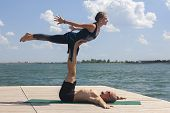Acro Yoga Concept. Pair Yoga. Couple Of Young Sporty People Practicing Yoga Lesson With Partner, Man poster