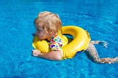 Little Baby Swimming In A Pool On Swimming Ring
