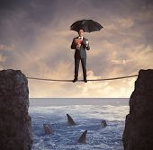 stock photo of dangerous  - Concept of insurance with businessman on the rope - JPG