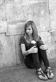 stock photo of pre-adolescent girl  - Sad teenage girl sitting on the ground in alleyway - JPG
