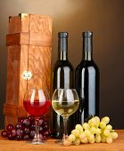 Wooden case with wine bottles on wooden table on brown background