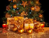 Picture of many golden presents boxes under luxury Christmas tree, beautiful adorned New Year spruce