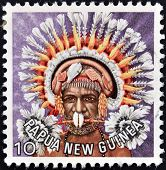 PAPUA NEW GUINEA - CIRCA 1977: stamp printed in Papua New Guinea shows a man in a feathered headdres