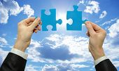 stock photo of reunited  - puzzle in hand isolated on sky background - JPG