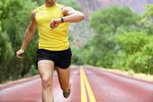Runner with heart rate monitor sports watch. Man running looking at his pulse outside in nature on r