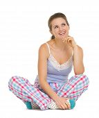 Thoughtful Young Woman In Pajamas Sitting On Floor And Looking O