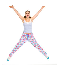 picture of peppy  - Smiling young woman in pajamas jumping isolated on white - JPG