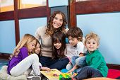Happy teacher sitting with children on floor in classroom