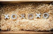 pic of xoxo  - Hugs and kisses symbols xoxo in a wooden gift box filled with natural raffia - JPG