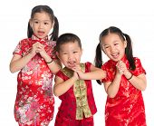 Little oriental children wishing you a happy Chinese New Year, with traditional Cheongsam standing i