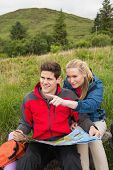 Cheerful couple taking a break on a hike to look at map with woman pointing in the countryside