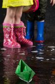 Green paper boat on the background of children feet wearing in colorful rubber boots