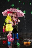 Little girl and boy hiding from the water under a pink umbrella and paper boats