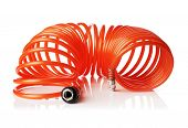 Orange red thin spiral air hose used for pneumatic tools. Isolated on white with natural reflection.