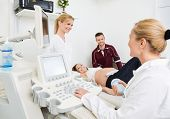 Female gynecologists and expectant couple undergoing ultrasound scan in clinic