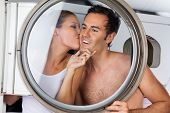 Loving woman kissing young man on cheek in laundry