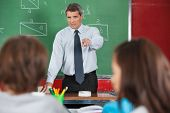 Angry male teacher pointing at students in classroom