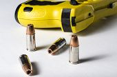 image of hollow point  - a close up of a police stun gun and bullets - JPG