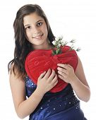 An attractive young teen in formal wear happily holding a red, heart-shaped pillow with a pocket ful