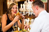 Couple - man and woman - in a fine dining restaurant they eat fast food, burger and fries - a large