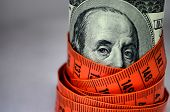 Dollar wrapped by orange tape