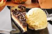 foto of cheesecake  - Closeup of a slice of gourmet turtle cheesecake with vanilla ice cream  - JPG