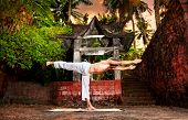 picture of virabhadrasana  - Yoga virabhadrasana warrior III pose by man in white trousers near stone temple at sunset background in tropical forest